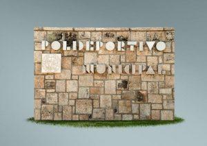 Rótulo y escudo en muro rústico